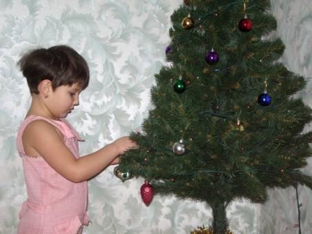 Это доченька наряжает елочку в нашем загородном доме