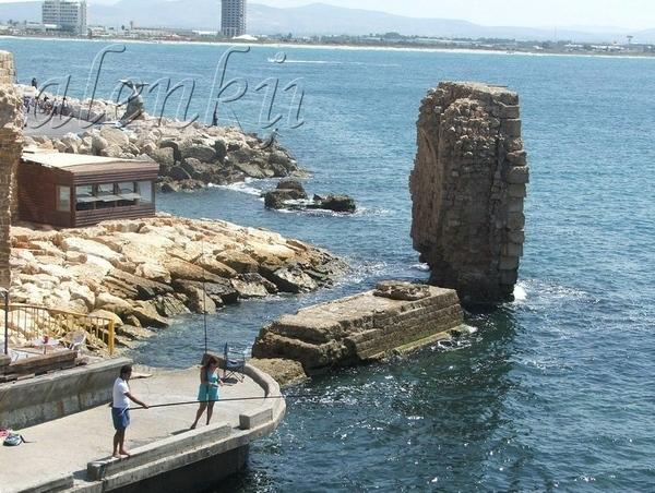 На отколовшейся когда-то стены сидят рыбаки да прохаживаются туристы
