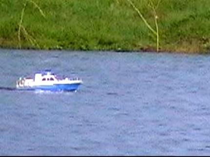 На противоположном береге, мальчик спустил на озеро игрушечный катер на дистанционном управлении