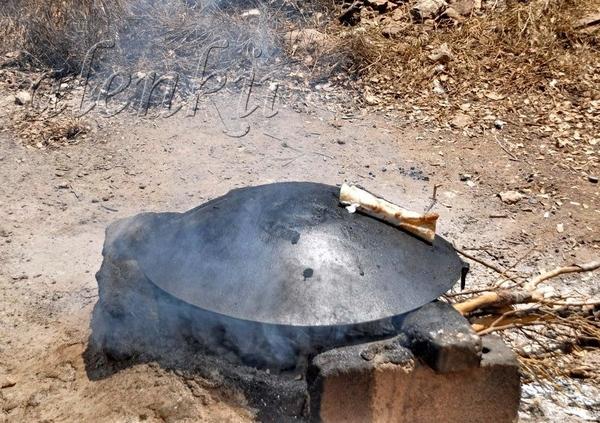 Продавец смазывает тонкую лепешку кисловатым сыром - лабане, посыпает смесью заатара с кунжутными с...