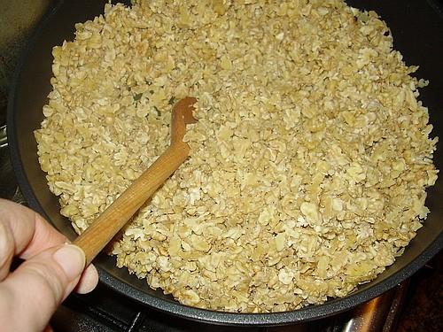 Бросьте порезанные орехи на глубокую (желательно чугунную) сковородку и немного их поджарьте
